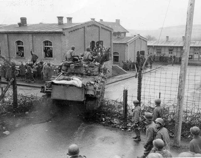 An American Sherman tank of Task Force Baum crashes through a gate at the Hammelburg POW camp during Patton's abortive attempt to rescue American soldiers and his son-in-law, Lt. Col. John K. Waters. Thomas Flynn was one of the POWs held at Hammelburg.