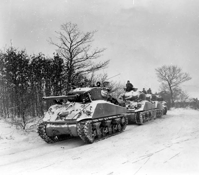 Four Sherman tanks with 76mm guns form a line along a snowy Luxembourg road. The 707th Tank Battalion helped bolster Flynn's defense of Hosingen—for a while.