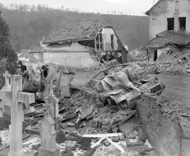 A Sherman tank from the 707th Tank Battalion lying on its side behind a knocked-out German Sturmgeschütz III at the cemetery outside Clervaux are mute testimony to the heavy fighting throughout Luxembourg.
