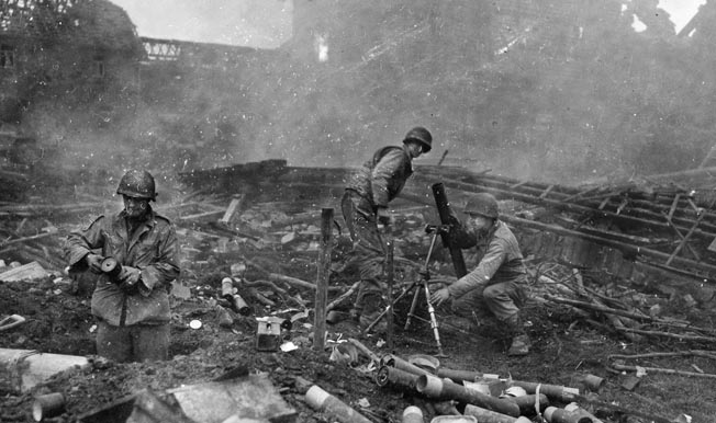 An 81mm mortar crew from the 22nd Infantry Regiment, 4th Infantry Division fires from the rubble of a village in support of rifle companies holding off a German counterattack at Grosshau, December 1, 1944.