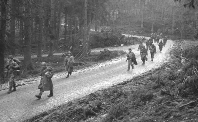 Men of the 13th Infantry Regiment, 8th Infantry Division advance along a muddy road through the dense forest. The 8th was brought in to relieve the hard-hit 4th Infantry Division, but it also was decimated by the tenacious German defense.