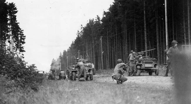 An American reconnaissance team takes cover as it goes into action against a German machine-gun nest concealed in the forest. A mortar team at left shells the German position.