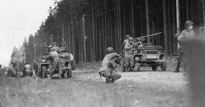 Taking up defensive positions in a clearing in the Hürtgen Forest, soldiers of the 28th Infantry Division prepare to engage the Germans. At left, a two-man team has just fired a round from a mortar.