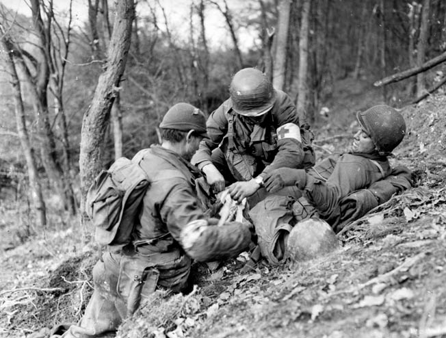 Medics of the 4th Infantry Division tend to a wound- ed GI. Evacuating the wounded was a difficult undertaking because they often had to be carried long distances to aid stations.