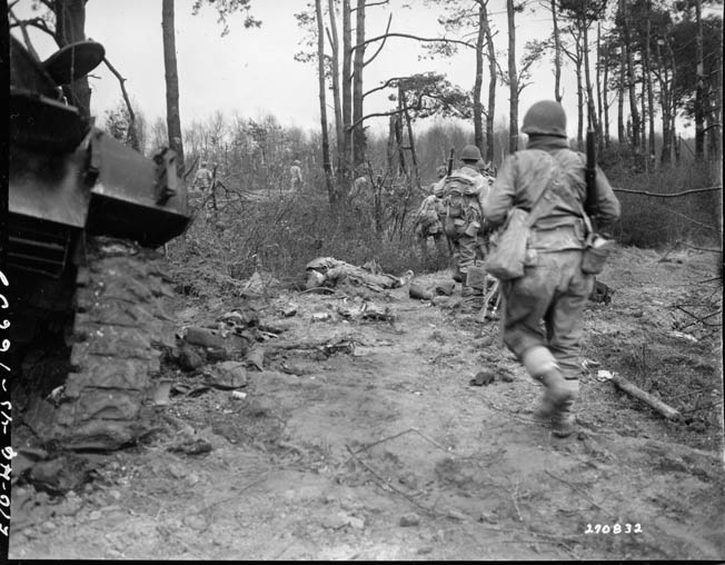 Soldiers of the U.S. 9th Infantry Division pick their way past a Sherman tank.