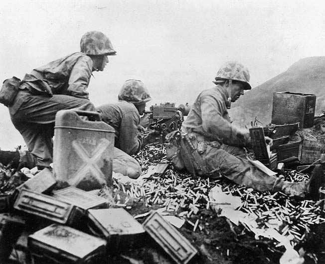 Marines fire their water-cooled, .30-caliber machine gun at the enemy at the foot of Mount Suribachi on L + 3.