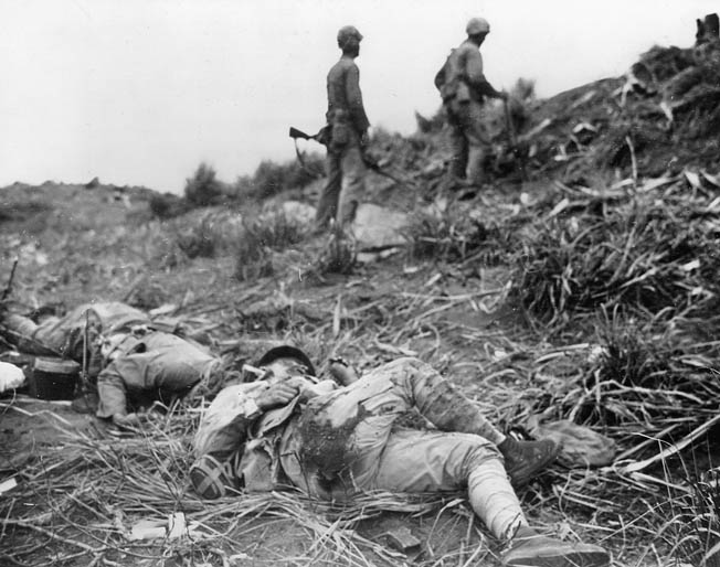 Japanese defenders lie dead as two Marines warily make their way up a hill toward their next objective.