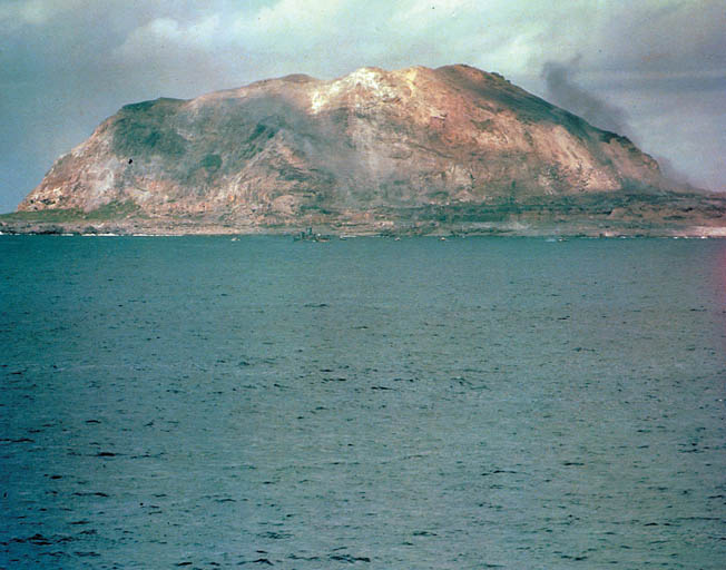 Like a giant, all-seeing monster, Mount Suribachi looms 556 feet above the invasion beaches.