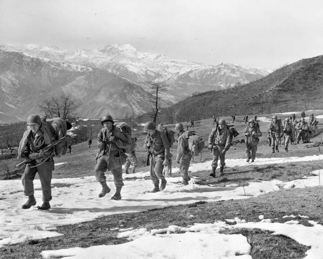 A line of 10th Mountain Division soldiers climbs Mount Belvedere, north of Florence, Italy, February 20, 1945. The hotly contested Riva Ridge is visible in the background.
