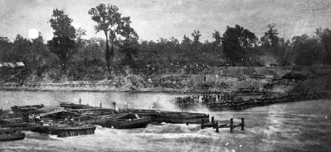 Union workers wade into the water to complete an improvised dam across the Red River. The dams raised the water level high enough to allow Porter's ships to retreat.