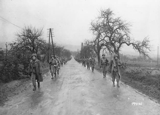Soldiers from the 90th Division's 358th Infantry advance down a rain-slickened road to meet the enemy at Fort Koenigsmacker, November 1944.