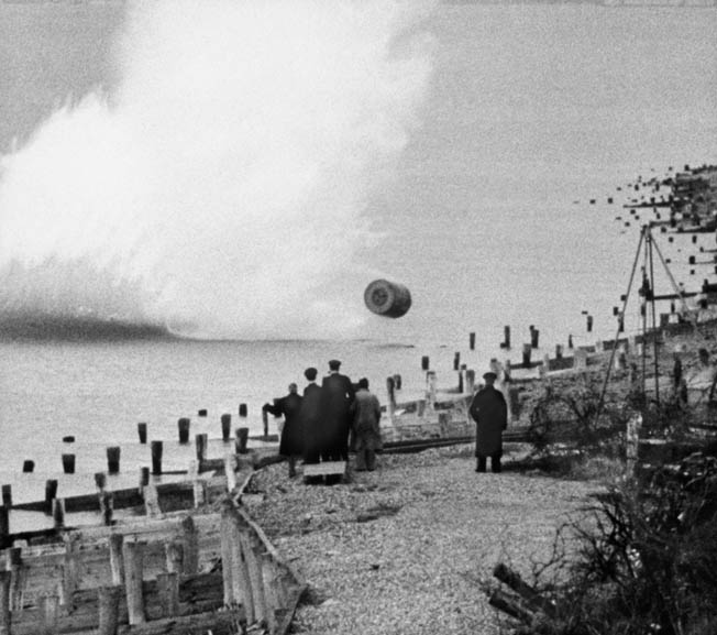 The bomb bounces toward the shoreline as observers, including inventor Barnes Wallis, look on.