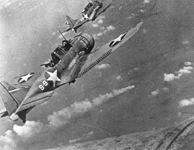 In one of the most famous images of the Dauntless from World War II, two SBD-3 dive-bombers from USS Hornet approach the burning Japanese heavy cruiser Mikuma during the early afternoon of June 6, 1942, near the conclusion of the Battle of Midway. Mikuma had been hit earlier by strikes from Hornet and Enterprise, leaving her fatally damaged and dead in the water. This photo was enlarged from a 16mm color motion picture film.