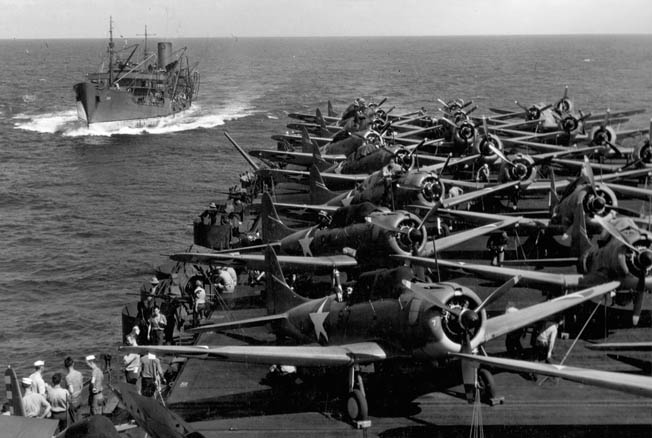SBD-3 Dauntless dive-bombers (without the folding wings of planes such as the Chance-Vought F4U Corsair and P-40 Avenger) crowd the deck of a U.S. Navy aircraft carrier during the summer of 1942.