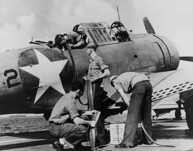 A groundcrewman loads linked M2 .30-caliber ammunition for a twin ANM2 mount into a Douglas SBD Dauntless at the USMC aerial gunnery school at MCAS El Centro, California.