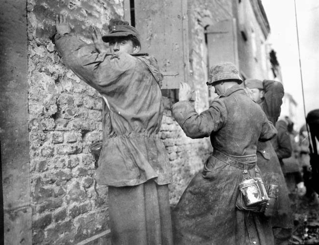 German prisoners captured by the 104th Division near Inden on October 12, 1944, keep their hands up as they wait to be searched. While guarding prisoners, Creamer accidentally discharged his pistol, nearly hiting them.