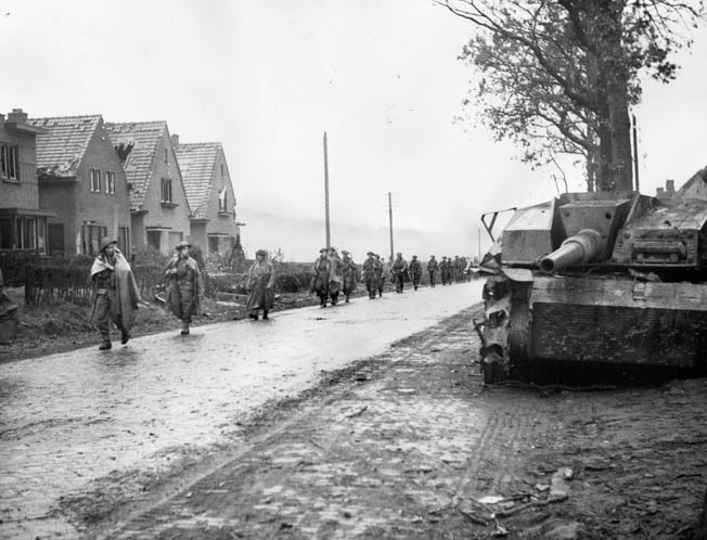 Canadian soldiers of the Calgary Highlanders march past a German Sturmgeschutz assault gun that has been knocked out during earlier fighting. This photo was taken in South Beveland during the advance against stubborn German resistance on Walcheren Island in October 1944.