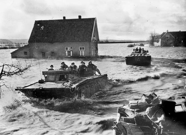 As they continue to battle German troops for control of the Scheldt Estuary, Canadian soldiers traverse a flooded area in an amphibious vehicle.