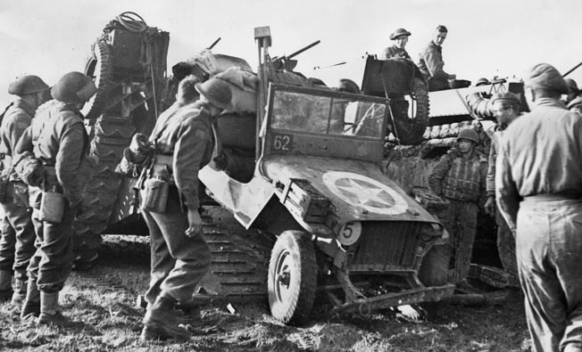 A Canadian II Corps jeep is backed into a landing craft prior to advancing across a waterway during the advance toward Antwerp