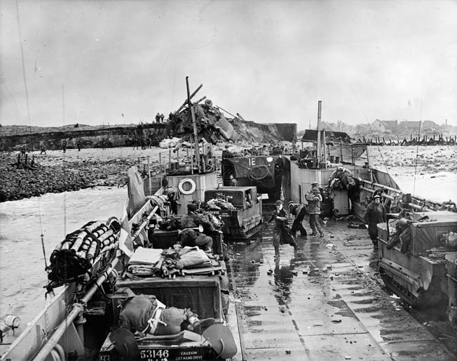 "Royal Marine Commandos in an amphibious personnel carrier (""Buffalo"") exit an LCT (Landing Craft, Tank) while a number of M-29 ""Weasels"" await their turn. The LCT has just beached at Westkapelle during the final phase of the battle."