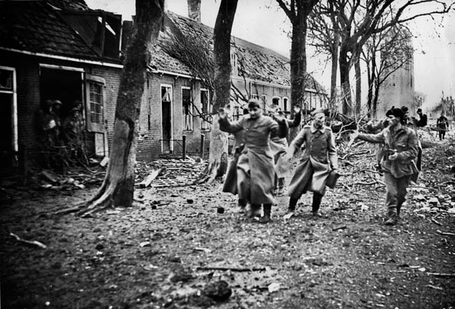 As the hard-fought campaign to clear the Scheldt Estuary of German resistance draws to a close, British commandos round up surrendering enemy soldiers in Westkapelle.