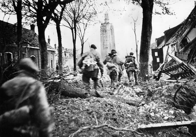 Men of No. 41 Commando dash through the ruins of Westkapelle toward the lighthouse on the western tip of Walcheren Island.