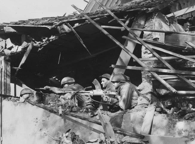 Soldiers of the 3rd Polish Infantry Brigade fire on Germans from a farmhouse destroyed during the fighting.