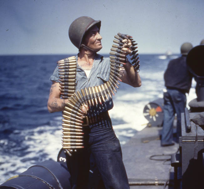 An American sailor shoulders .50-caliber ammunition as he reloads one of the heavy machine guns aboard a PT boat somewhere in the Pacific.