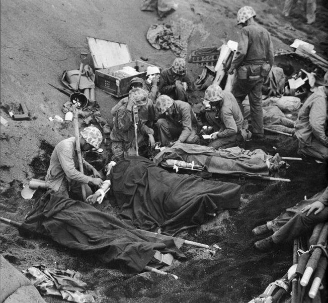 Navy Chaplain Lt. (j.g.) John H. Galbreath (right center) kneels beside a badly burned Marine as Navy doctors and corpsmen administer to the wounded at a makeshift Iwo Jima aid station, February 20, 1945.