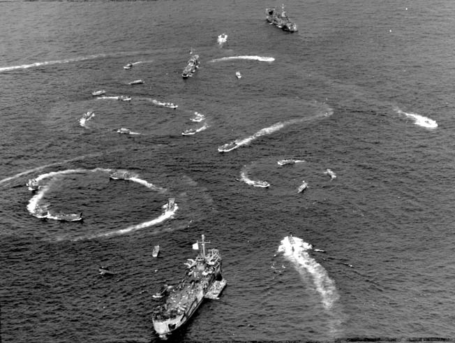 Landing craft circle as they wait for word to deliver their human cargoes to the beaches of Iwo Jima. Larger landing ships, LSTs (Landing Ship, Tank), that disgorged the troop-laden craft are also visible in this photograph.