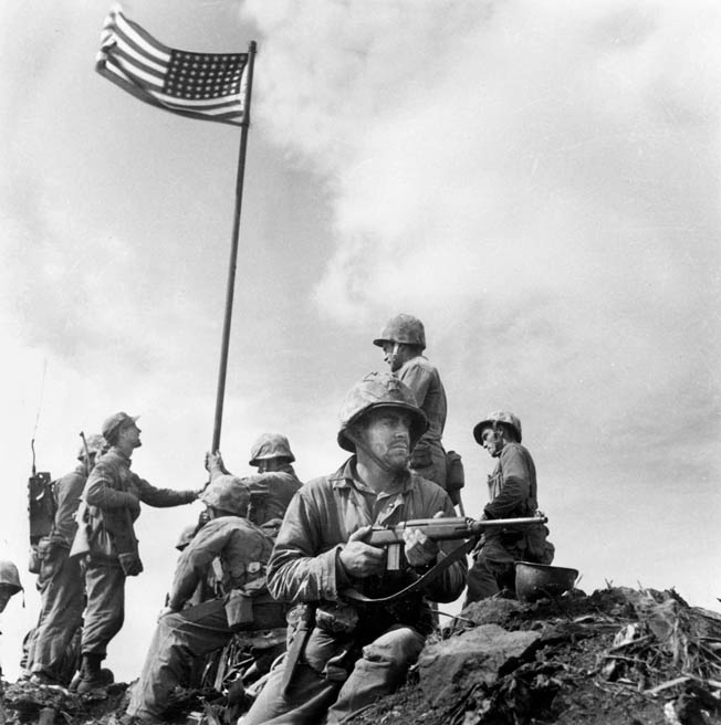 The first flag raising, with the smaller flag carried ashore by Company E, 2nd Battalion, 28th Marines, February 23, 1945.