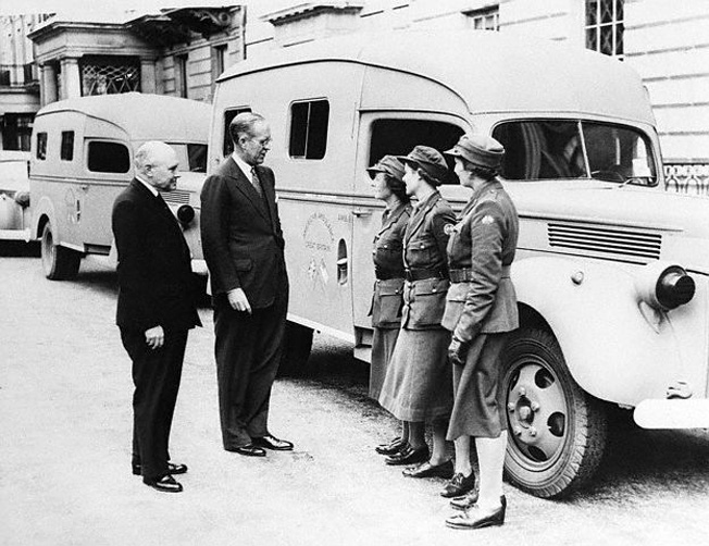 "Kennedy, center, talks with volunteer drivers of the ""American Ambulance Unit of Great Britain"" in London, July 1940. Kennedy donated the money to purchase one of the vehicles."