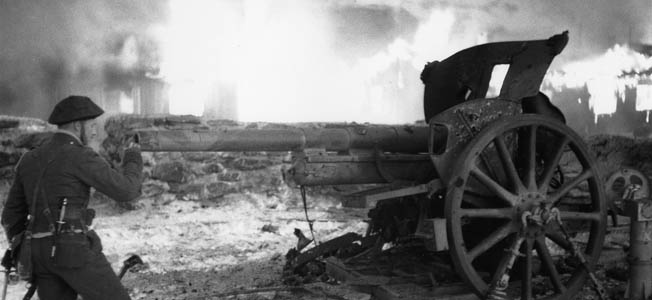 Jack Churchill inspecting the wreckage of a German field gun following action against elements of the Wehrmacht in France.