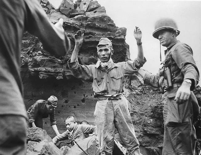 Dazed and shell-shocked, the first of 21 Japanese to emerge from a cave surrender in March 1945. Out of a garrison of 21,000, only about 200 Japanese were taken prisoner.