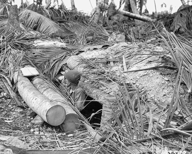 After its original occupants have been killed, an American soldier stands in the entrance to a Japanese bunker on Butaritari. Heavy coconut logs that were used to reinforce the enemy strongpoint.