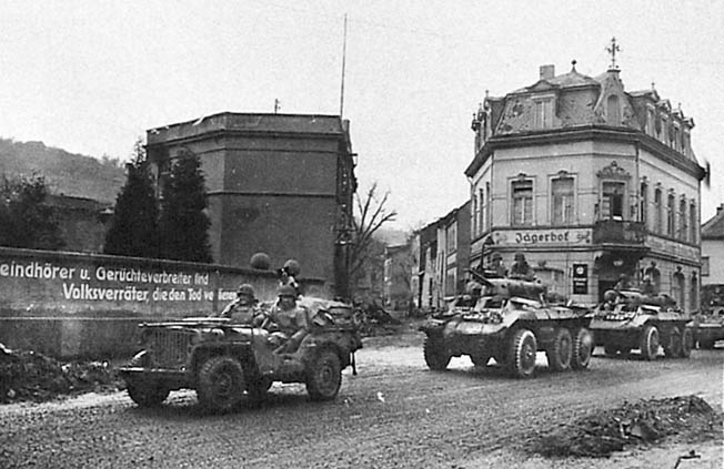 American jeeps and armored cars pause in Remagen before heading eastward across the bridge and into the heart of Germany.