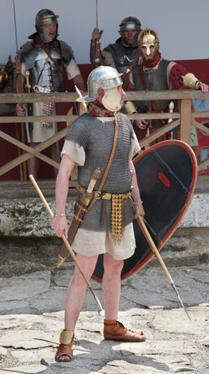 A Roman reenactor wearing chain mail, armed with a gladius sword and pilum javelins.