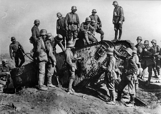 German infantry climb over the remains of a British Mark IV tank knocked out during the Battle of Cambrai.