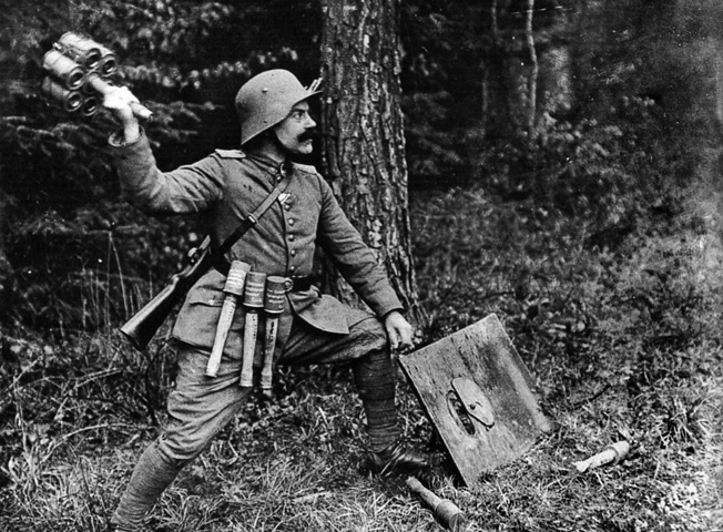 A mustachioed German solider flings a Geballte Ladung, or bundle of grenades, at an Allied tank or bunker.