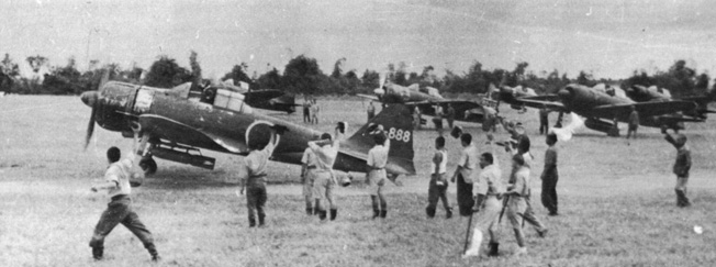 In this photo, a Japanese kamikaze pilot, his canopy open, taxis on Clark Field toward a rendezvous with death during an early suicide raid in October 1944. Ground crewmen shout encouragement to the doomed pilot. In the beginning, kamikaze raids were conducted by volunteers. Later, pilots were ordered to carry out the suicide missions.