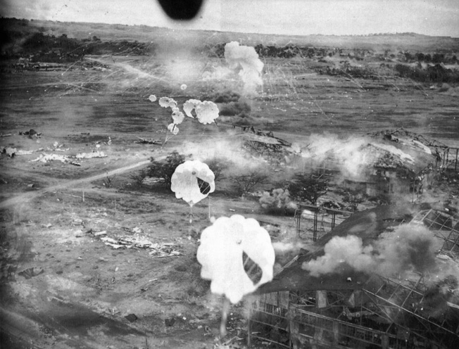 Lieutenant John T. Cooper flies his bomber low over the wreckage of the main hangar complex at Clark Field. The facility has sustained heavy damage, and smoke rises from a phosphorous bomb dropped among Japanese aircraft earlier in the raid.