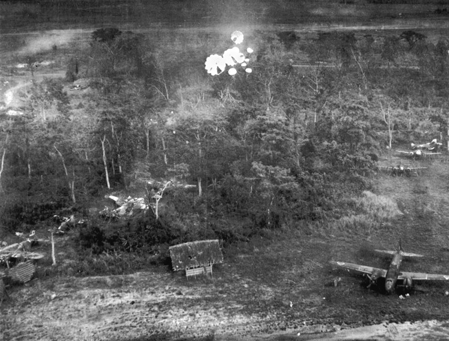Camouflage has proven to be little protection as parafrag bombs from American aircraft of the 498th Bomb Squadron, 345th Bombardment Group descend upon these Japanese planes on the ground at Clark Field in the Philippines.