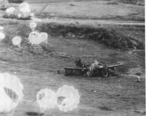 The parachutes attached to American fragmentation bombs are clearly visible in this photo of Japanese aircraft parked on the ground and under attack at Clark Field in the Philippines. Note the camouflage around the engine cowling of the plane at center.
