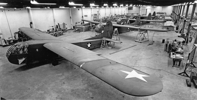 Brand new Waco gliders undergo the final steps in the assembly process on the floor of the Pratt, Read Soaring Company's manufacturing facility in Deep River, Connecticut. Before the war Pratt, Read manufactured a variety of parts for pianos, including keyboards.