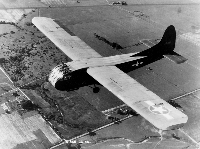 A Waco CG-4A glider is shown in flight. With its 48-foot-long fuselage, the CG-4A could carry up to 13 soldiers, a Jeep, or a small artillery piece.