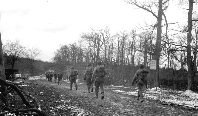 Soldiers of the 2nd Ranger Battalion slog their way along a muddy road in the Hürtgen Forest. These Rangers are on their way to Hill 400, the scene of a fierce stand against repeated German attacks.