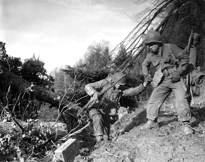 Fully loaded with gear, a soldier of the U.S. 4th Infantry Division helps a buddy negotiate the difficult terrain in the Hürtgen Forest. The densely wooded area compounded the difficulty of the action there, and tree bursts rained shrapnel and wood splinters on the troops.