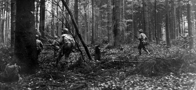 Soldiers of the 28th Infantry Division hurry through a wooded area of the Hürtgen Forest  near the town of Voosenack,  Germany. The 2nd Ranger Battalion was attached to the 28th Division during the fighting in the Hürtgen Forest.
