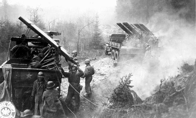 Men of the 18th Field Artillery Battalion, V Corps reload their rocket launchers in the Hürtgen Forest. Accurate and deadly American artillery fire was instrumental in holding the positions of the 2nd Ranger Battalion on Hill 400.