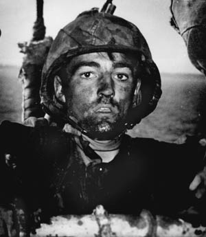 As he climbs aboard a transport off the island of Eniwetok, a U.S. Marine wears the expression of a fighting man who has endured continued hardship.